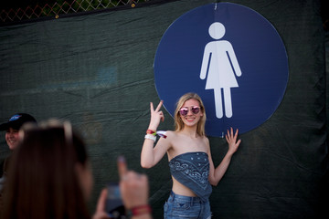 A woman poses for a portrait beside the portable restroom entrance during the Firefly Music Festival in Dover, Delaware U.S.