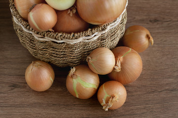 Harvest of onions. View from above. Onion bulbs in a wicker basket and next to it. Vegetables for a healthy diet.