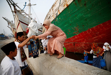 People arrive on a small ferry boat to attend prayers to celebrate Eid al-Fitr, marking the end of the holy fasting month of Ramadan, at Sunda Kelapa port in Jakarta,