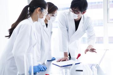 男性研究員がパソコンを見ながら説明をしている研究室の風景