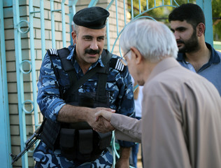 A Sunni Muslim and policeman exchange greetings after Eid al-Fitr prayers to mark the end of the fasting month of Ramadan at a Sunni mosque in Baghdad