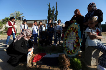 People visit the grave of Palestinian nurse Razan Al-Najar, who was killed as she tried to help a wounded protester at the Israel-Gaza border, on the first day of Eid al-Fitr holiday in Khan Younis in the southern Gaza Strip