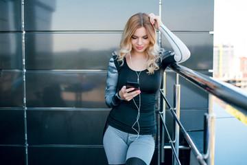 Woman in sport wear using mobile phone