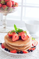 Breakfast with pankakes from whole wheat flour and fresh berries, selective focus