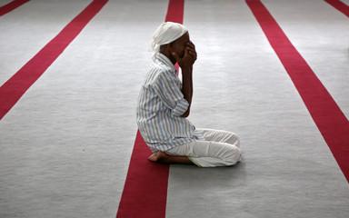 A man prays during Eid al-Fitr prayers at a mosque in Kochi