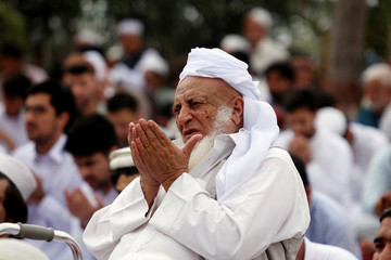 A man holds his palms together along with others during Eid al-Fitr prayers at a park in Peshawar, Pakistan