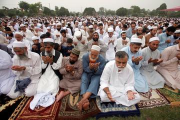 Men hold their palms during Eid al-Fitr prayers at a park in Peshawar, Pakistan