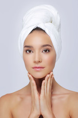 Beautiful woman in a white towel on a head.