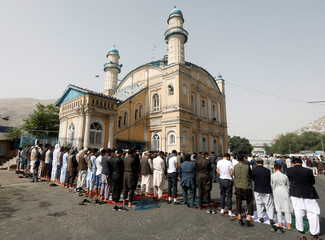 Afghans take part in morning prayers to celebrate the first day of the Muslim holiday of the Eid al-Fether, in Kabul, Afghanistan