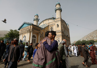Afghans greet each other outside the Shah-e Doh Shamshira Mosque, on the first day of Eid al-Fitr, which marks the end of the holy month of Ramadan, in Kabul, Afghanistan