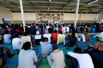 Muslim migrants attend Eid al-Fitr prayers to mark the end of the holy fasting month of Ramadan at a detention centre in Tripoli