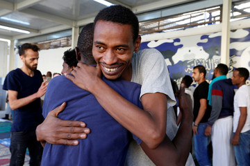 Muslim migrants exchange greetings after Eid al-Fitr prayers to mark the end of the holy fasting month of Ramadan at a detention centre in Tripoli