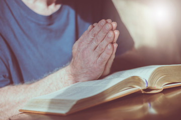 Man praying with his hands over the bible