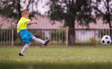 Boy kicking football on the sports field