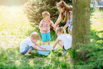 Four enthusiastic children enjoying and playing with raw fish in basin outdoor in sunny summer day. Childhood, friendship and adventure concept. Cheerful fuss. Sun glare effect