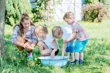 Four enthusiastic children enjoying and playing with raw fish in basin outdoor in sunny summer day. Childhood, friendship and adventure concept. Cheerful fuss.