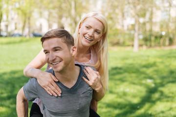 lachender Mann trägt seine Frau Huckepack durch den Park