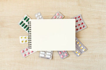 Paper notepad mock up in frame of various blisters with multi-colored tablets and capsules on wooden table. Doctor desk background, horizontal medical concept copy space, white mockup