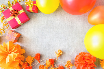Birthday party background with festive decor, orange, yellow and red ribbons, gift boxes, balloons, garland, pompoms on neutral fabric. Colorful celebration background, copy space, Flat lay, top view.