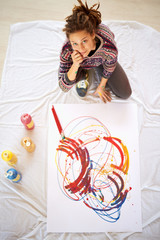 Aerial view of Artistic girl sitting in studio and paint in her atelier.