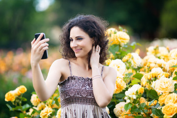 A portrait of Caucasian woman with dark curly hair taking selfie near yellow rose bushes in a rose garden, video call, chat, smile