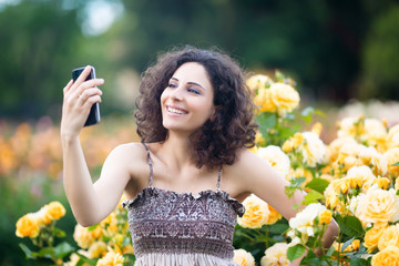 A portrait of Caucasian woman with dark curly hair taking selfie near yellow rose bushes in a rose garden, video call, chat, smile with teeth