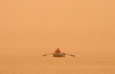 A man rows a boat amidst haze and dust in the waters of Sukhna lake in Chandigarh
