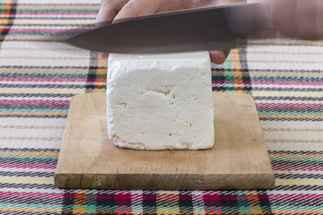 Cutting traditional bulgarian white cheese
