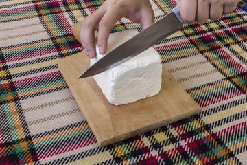 Cutting traditional bulgarian white cheese
