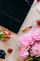 Beauty flat lay with a desktop, cosmetics, accessories and peonies on a marble background