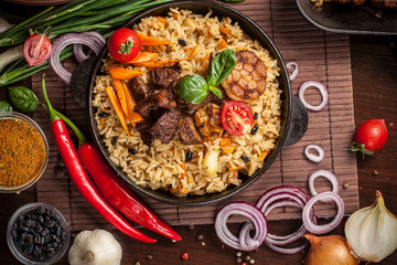 The concept of oriental cuisine. Homemade Uzbek pilaf from lamb served in cast iron cookware. Copy space.