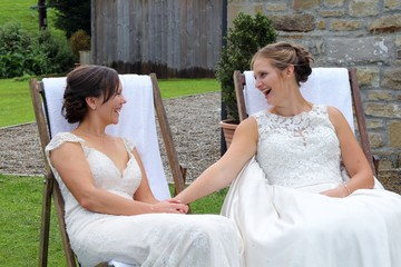 Same sex brides talking and sat on deck chairs at the end of their wedding day