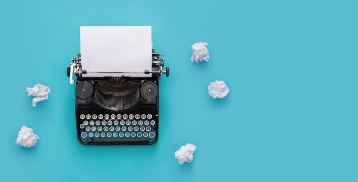 Vintage typewriter over blue background with copy space
