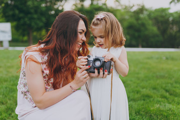Joyful woman in light dress and little cute child baby girl take picture on retro vintage photo camera in park. Mother, little kid daughter. Mother's Day, love family, parenthood, childhood concept.