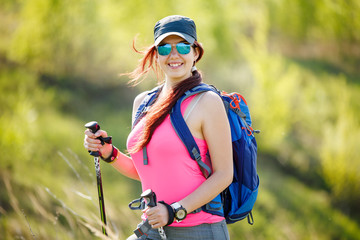 Photo of smiling female athlete with walking sticks and backpack with blurred background