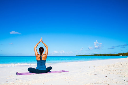Beautiful young woman practicing yoga on the beach on Bahamas iseland.