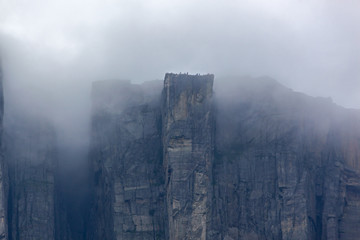 View of Preikestolen steep cliff in fog from the Lysefjorden, Rogaland, Norway