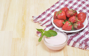 Juicy strawberry on a plate on a wooden table