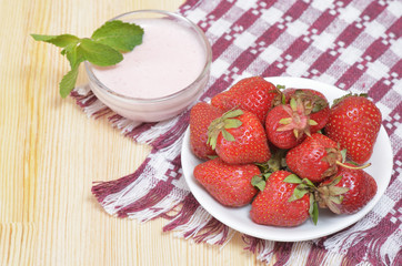 Large ripe strawberries on a white plate and sauce with mint leaf