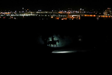 Border Patrol agents on horses track a man along the Rio Grande River after he illegally crossed into the U.S. from Mexico in Sunland Park, New Mexico