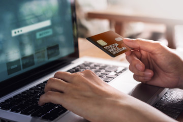 Customer using Credit Card and Computer laptop to Shopping Online. Close-up shot and Selective focus on left hand