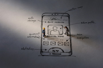 User Experience Concept. present by two Miniature Figure of Businessman standing on Paper of Interface Design Sketch at Night. Overtime Work
