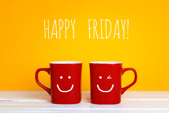 Two red coffee mugs with a smiling faces on a yellow background with with the phrase Happy friday.