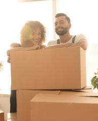Happy couple honeymooners standing near boxes