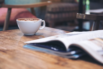 Closeup image of a magazine with coffee cup on wooden table in cafe