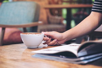 Closeup image of a woman reading a magazine with coffee cup on table in cafe
