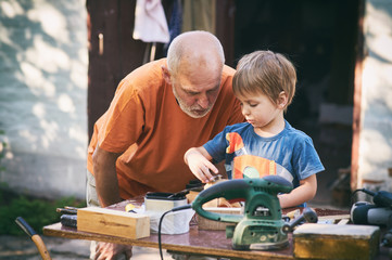 Grandfather and his grandson having fun in the outdoor workshop
