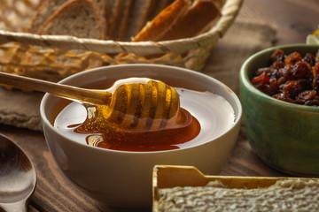 Honey pot and dipper at rustic table with bread, raisins and Honey comb