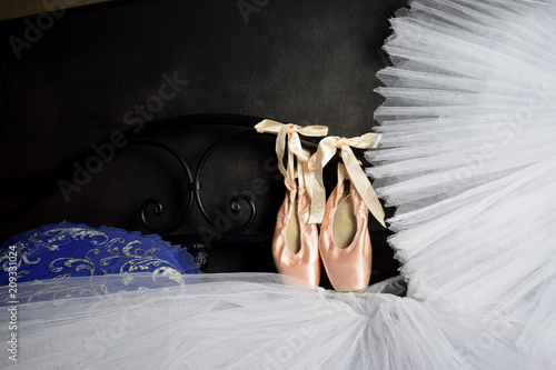 3cf74cb3a1a9 Ballet accessories pointes hanging on the back of the bed and a ballet tutu  lying on the bed on a black background of the wall