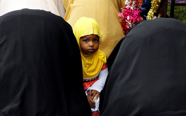 A Muslim child participates in Eid al-Fitr prayers to mark the end of the holy fasting month of Ramadan at the Sir Ali Muslim Club Ground in Nairobi, Kenya